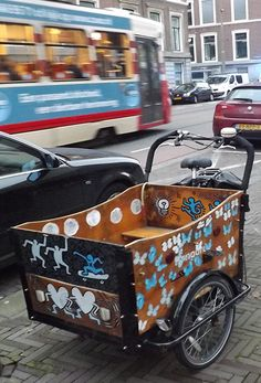 BIKE SHOPS THE HAGUE - DELFT AREA A vibrantly painted cargo bike with Keith Haring-inspired artwork seen in The Hague. Find a list of bicycle shops, selling new and used bikes and repairing broken ones, in Wassenaar, Voorburg, Leidschendam, Rijswijk, Delft and surroundings here... https://www.angloinfo.com/south-holland/directory/south-holland-bicycle-shops-service-the-hague-area-811