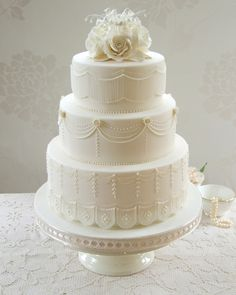 Ivory wedding cake decorated with piped string work, swags and piped lace - and adorned with hand-crafted lily of the valley and cream roses - perfectly in tune with a grand country house wedding setting.
