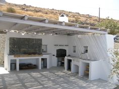 Open air kitchen with bbq spot, oven and marble sink. Concrete counters covered by cement mortar. Paros, Greece