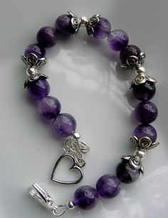 * Genuine Semi Precious Amethyst stones 8 mm * Tibetan Silver flower bead caps * Heart Dangle on Extension * Sterling Silver Wire Guardians for durability * Sterling Silver Extension Chain * Crimp covers Size: 7 inch with 1 inch extension All of my jewelry comes in a pretty organza gift bag or gift box with an information card detailing each stone and its healing properties.  Please be sure to see my Earrings Section for matching Amethyst earrings!! If you dont see any you like, message me…