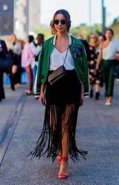 Street style look com saia midi franjas preta, regata seda, bomber jacket verde…