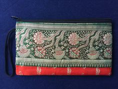 This is a beautiful padded bag/case made with 100% vintage silk from Pushkar, Rajasthan, India, where I study classical Indian dance. It is 9x5 (23cmx13cm), perfect size for small notepads, pens, chapsticks, keys, cell phones... I put most of my things in there so that they are not lost in a big bag. It is a perfect pouch to use when you are going out - its light weight and yet it can hold a good amount of personal items! Elaborate embroidery and vibrant colors, I discovered that the col...