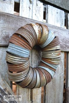 Rusty canning jar lid wreath on outdoor reclaimed wood shed door, via Funky Junk Interiors