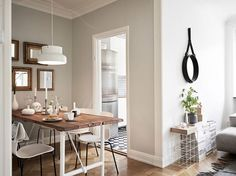 Swedish interiors-dining room Simple wooden plank table, grey walls, collection of wooden framed mirrors above table for warmth and light