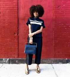 Street style de Kai Avent-deLeon com blusa e calça azul marinho + mocassim dourado.