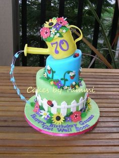 3 tiered garden themed cake with watering can on top. Dripping water technique is really cool!