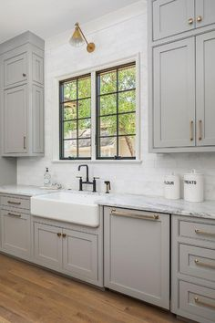 Oil rubbed bronze hardware on light gray cabinets in a transitional kitchen fitted with a farmhouse sink under a window surrounded by white brick stacked backsplash tiles. White Farmhouse Sink, White Kitchen Sink, Gray And White Kitchen, Kitchen With Farmhouse Sink, Farmhouse Style, White Brick Backsplash, Gray Kitchen Backsplash, Contemporary Kitchen Backsplash, Repainting Kitchen Cabinets