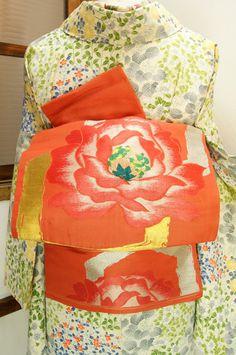 珊瑚のようなオレンジ色に近いこっくりとしたピンク色の地に、アールデコデザインを思わせるモダンな六角形の金銀のモチーフと、ぱっと花ひらく大輪の薔薇が織り出された大正ロマン・昭和レトロな華やぎかおる名古屋帯です。