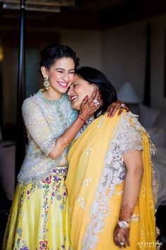 Mother of the Bride - Bride in a Yellow Floral Lehenga with a White Sequinned Jacket and the Mother in a Yellow Saree with Lace Borders | WedMeGood #wedmegood #motherofthebride #motherofthebrideoutfit #yellow #mehandioutfit #sangeet