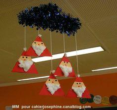 Pères Noël en triangles accrochés dos à dos et pendus à un cintre, lui même enroulé d'une guirlande de Noël