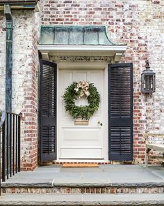 Decorated with a green wreath for the holidays, Jane Schwab's simple, elegant front entry features lime-washed brick, black shutters, and an aged copper overhang. Photography by Laurey W. Glenn