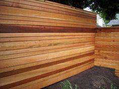 multi-tone natural colored horizontal fence. Variable slat size.