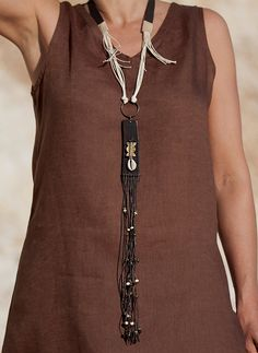 Vintage leather pendant : upcycled industrial leather strap, waxed cotton threads with ethnic small beads, cauri shell and baule bead, brass ring.  AMALTHEE CREATIONS