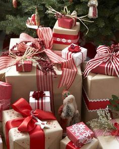 Brown paper wrapped gifts become beautiful with the use of fabric bows and sprigs of green.