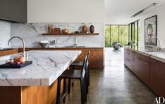 Marble countertops complement walnut-veneer cabinetry and polished concrete floors in the kitchen   archdigest.com
