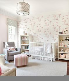 Pink and gray nursery design fitted with a white crib dressed in a white ruffled bed skirt against a wall layered with Cole & Son Flamingos Pink/White Wallpaper.