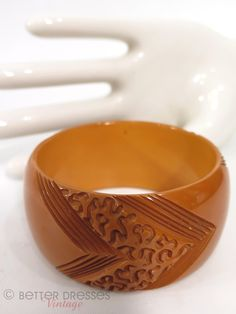From the 1940s, an extra-wide bangle bracelet in deep butterscotch (or peanut butter) opaque bakelite. Nicely carved at intervals with chevrons and squiggles. From the Huntington estate. Labels: none