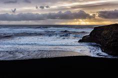 Black sand beach sunrise - Sunrise by Black sand beach in southern Iceland, With sunbeams over the ocean