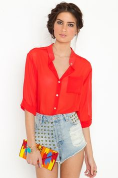 I love the bronze embellishment on the high waisted jean shorts and the mango-red blouse gives her look the perfect pop!