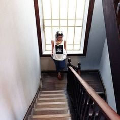 """Foto menina em escadaria de madeira rústica usando uma blusa branca com a frase """"This shirt is special and you can't have it""""."""