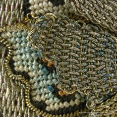 A butterfly motif is overlaid with detached needle lace details in gold and silver filé. Coiled gilt silver strip outlines the shape of the butterfly. . Magnification 10x. Image by Cristina Balloffet Carr. early 17th century, British. Canvas worked with silk and metal thread, glass beads, spangles; Gobelin, tent, and detached buttonhole stitches; silk cord and silk and metal thread tassels. 5 1/8 x 5 1/8 in. (13 x 13 cm), excluding tassels and draw cord.(29.23.15)