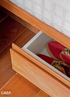 Em metragens enxutas, cada centímetro vale ouro – inclusive aqueles embaixo dos móveis. Aqui, a cama, feita sob medida (Madform), ganhou quatro gavetões recuados a 10 cm da base, esconderijo perfeito para os calçados.
