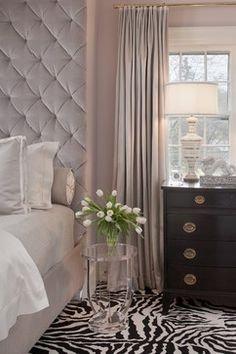 A mile high headboard, sumptuous curtains and clear night stand enhance the feeling of dreamy glamour, while the zebra print rug wakes things up a bit with its bold black and white pattern.