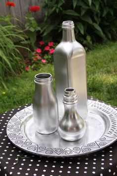 Create your own tablescape using glass bottles and metallic spray paint. These are an olive oil bottle, frappucino bottle and soy sauce bottle painted metallic silver.  Simple but looks elegant!