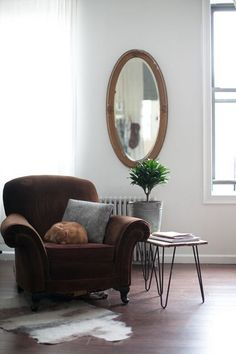 """Sneak Peek: Adrienne Antonson and Kevin Murphy.""""No matter how small my studio is, I always have a thinking chair. As you can see, Magda does most of the thinking. The vintage armchair matches our couch, the rug is another felted alpaca piece from my farm days and the gilt mirror is a family antique."""" #sneakpeek"""