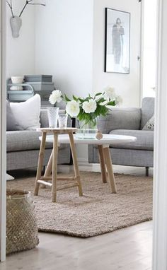 Glass vase, wooden stool, grey fabric sofa and white tea table