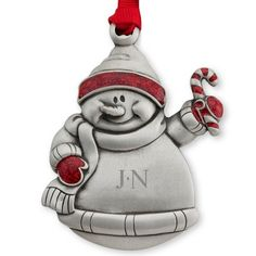 Made in the USA and crafted from lead-free genuine pewter, this ornament features a festive snowman with red glitter accents on the hat, gloves and candy cane. This ornament is tied with a red grosgrain ribbon and packaged in a red gift box. Engrave a name and special message on the center of the ornament.  https://www.thingsremembered.com/product/Genuine-Pewter-Snowman-Ornament/178405.uts
