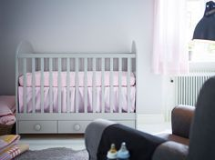 A light grey baby cot with three floor drawers