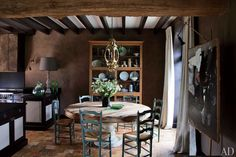 In the dining area of a French farmhouse, a C. Jeré ceiling light is suspended over a custom-made table with a 19th-century Thai base; the set of 1940s straw-seat chairs is from Jean-Louis Deniot's Paris shop, Onsite Antiques.