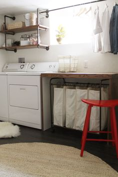 basement laundry room -- I like the simplicity of this room, the wooden folding table, the shelves over the washer/dryer, the drying rack, the laundry sorter under the table (genius, then you don't have to see the messy laundry!), and the bright red stool