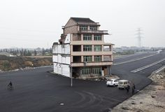 Lone home still stands amid new pavement as duck farmer in China goes up against city planners.