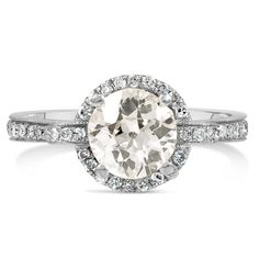 The Brigid Ring - This delicate Retro-era ring features an old mine cut diamond surrounded by forty-eight single cut diamond accents. Scroll and milgrain detailing in a white gold setting complete this gorgeous ring (approx. 1.44 total carat weight).