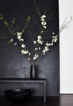 The Art of Display. Love the white flowers in contrast to the black painted wall, black console & vase.