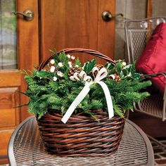 Deluxe Winter White Basket - Each one is created by hand, the Noble Fir and Western Red Cedar adorned with variegated Holly, Ponderosa Pine cones, faux white berries, and a bright white holiday ribbon! These unique evergreen compositions possess an understated beauty subtly reminiscent of snow-blanketed hills.   This product is no longer available, however click the image to see this year's Evergreen Centerpieces!