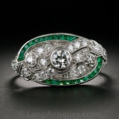 From the 1920s-30s, an exquisite handcrafted Art Deco dinner ring featuring European-cut diamonds and emerald calibre. This elegant oval-shaped ring is centered with a quarter-carat, bezel-set European-cut diamond and sparked with smaller diamonds set amidst the pierced and milgrained details, with a dramatic splash of color added from the border of emeralds. This fabulous, original Art Deco ring is also fully hand engraved along the gallery and ring shank.