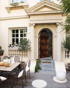 Stucco house with arched, wooden door and heavy moldings - Barcelona, Spain, LOVE the Tuscun style of this house and the attention to detail!