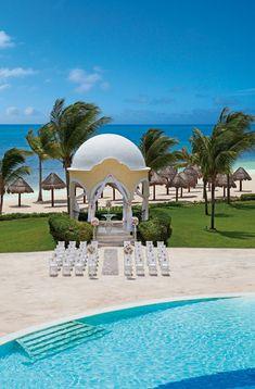 Weddings Riviera Maya - Secrets Capri Riviera Maya, Puerto Morelos, Mexico -  Poolside wedding ceremony with ocean backdrop.