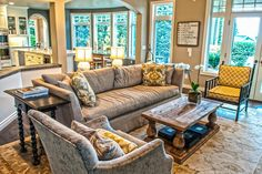 A crushed velvet armchairs lend a splash of elegance and sophistication to this otherwise casual, comfortable living room. Plenty of windows ensure a bright, cheery atmosphere.