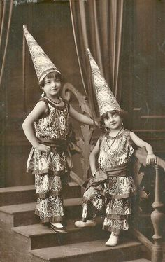 Two girls wearing costumes and pointy hats (real photo postcard)