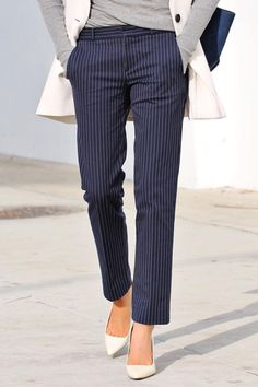 Fifty Two Thursdays keeps her look classic in our navy and white pinstripe straight leg pants. She pairs them with a white vest and a gray sweater. She adds an extra bit of glam with a pair of white pumps | Banana Republic