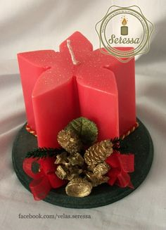 Vela con forma de nochebuena sobre base redonda con adorno navideño.