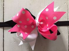 You are looking at a Minnie Mouse-inspired triple loop hair bow in pink polka dots, black and white attached to a coordinating black headband. The