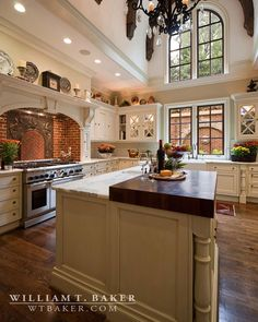 This kitchen features an unusual barrel vaulted ceiling with curved beams. Note the brick behind the cooktop with an applied iron detail.