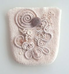 Small purse in nuno felt, embellished with motifs in crochet, lace embroidered Romanian, frivolity and some old buttons.