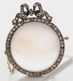 A beautiful antique Fabergé brooch, set with a moonstone surrounded by diamonds, with a diamond ribbon to the base.