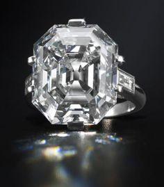An elegant diamond single-stone ring, circa 1935 The Asscher-cut diamond, weighing 19.56 carats, within a six-claw setting, between baguette-cut diamond shoulders.